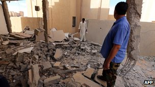 File pic: Libyan men inspect a destroyed building in Bani Walid on 11 October 2012