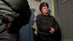 Russian Interior Ministry officers stand guard by the entrance door of opposition leader Sergei Udaltsov's apartment