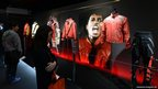 Journalists look at items from a collection of US pop star Michael Jackson's costumes
