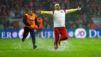 A Polish football fan runs across the wet pitch followed by security during heavy rain as the World Cup 2014 Group H qualifying match between England and Poland was postponed