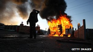 An activist looks on in front of a burning caravan, which was set ablaze by activists to be used as a barricade, as evictions begin at Dale Farm travellers camp 