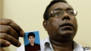 Quazi Mohammad Ahsanullah holds a portrait of his son in Dhaka, Bangladesh 18 October 2012