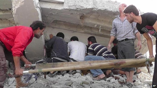 Syrian citizens search under rubble to rescue people from a building that was destroyed after an air strike in Idlib province, northern Syria, 17 October 2012 (image provided by Idlib News Network and authenticated based on its contents and other AP reporting)