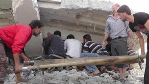 Syrian citizens search under rubble to rescue people from a building that was destroyed after an air strike in Idlib province, northern Syria, 17 October 2012