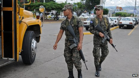Honduran soldiers stand guard at a bus stop in Tegucigalpa