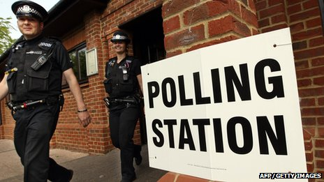 Police officers walk out from a community centre doubling as a polling station at Elvetham Heath near Fleet, Hampshire, on 5 May 2011