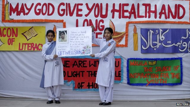 Students hold a placard as they attend special prayers for the recovery of Malala Yousufzai
