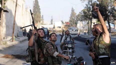 Rebel fighters point to the sky as a Syrian army helicopter flies overhead in the town of Maarat al-Numan