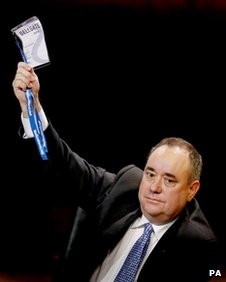 Alex Salmond holds aloft his voting card