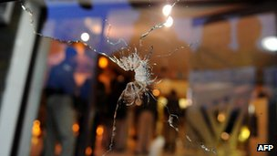 Indian police stand behind a bullet-shattered glass door at a hotel near Srinagar, 19 October