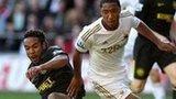 Swansea's Jonathan de Guzman (r) of battles with Wigan's Jean Beausejour