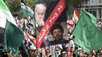 Thousands of people carry flags, including Syrian opposition flags, and a banner with images of Lebanon&quot;s Hezbollah leader Sayyed Hassan Nasrallah (bottom) and Lebanese Prime Minister Najib Mikati as they gather in downtown Beirut