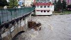 People walk on a bridge above the rain-swollen River Gave in Lourdes, 20 October