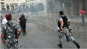 Security forces run after protesters.