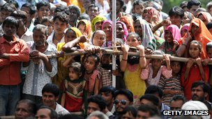 Villagers look on as Narendra Modi addresses them near Ahmedabad on 11 October  2012