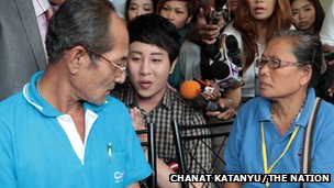 Thanat &quot;Dr Pop&quot; Natveerakul (centre) apologises to the parents of Kratae Eiamyai at a Bangkok police station.