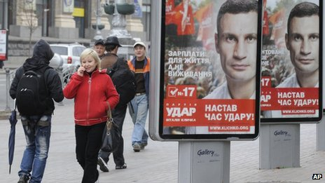 People walk past election posters of Ukrainian boxer and Chairman of the Ukrainian Udar Party, Vitali Klitschko in Kiev, Ukraine, Thursday, Oct. 18, 2012.