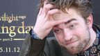 Actor Robert Pattinson gestures as he arrives for a fan event