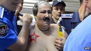 A Femen activist dressed as Belarusian President Alexander Lukashenko in Kiev