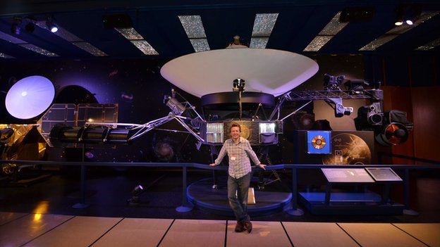 Chris Riley next to the Voyager model at JPL
