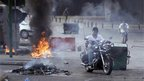 Man rides motorcycle between burning tires and rubbish containers in Beirut (22 Oct)