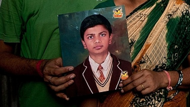 Pinki and Dinesh Kumar Singh pose with a photograph of their missing child