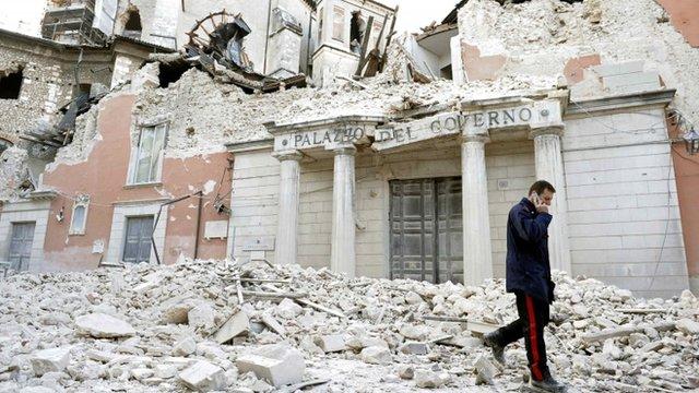 Italian military carabinieri walks on debris past destroyed buildings after an earthquake