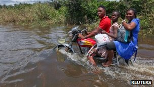 A man rides a motorcycle with passengers along a flooded road in the Patani community in Nigeria's Delta state - 15 October 2012