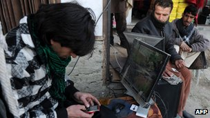 An Afghan man waits to upload songs on his mobile phone at a roadside shop in Kabul