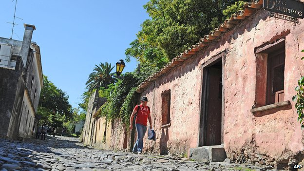 Tourist walks down a street in the old quarter of Colonia del Sacramento, Uruguay