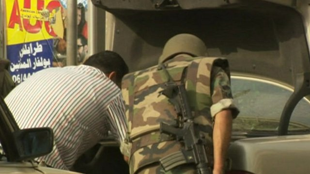 Lebanese soldier and civilian looking in car boot