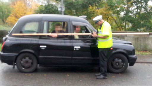 A police officer talks to the driver of a taxi which has a 10ft wooden pole running along the side