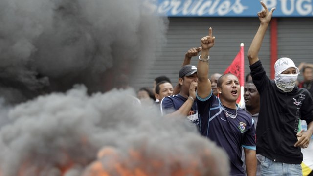 Demonstrators gather at a road block during an ongoing violent protest in Colon City