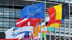 """European Union flag fly amongst European Union member countries"""" national flags in front of the European Parliament"""