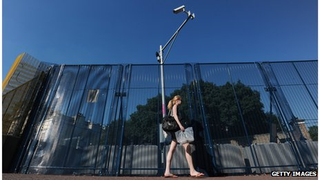 A woman walks past a CCTV camera
