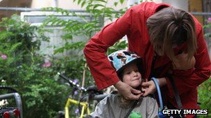 Berlin mother tightens child's cycle helmet