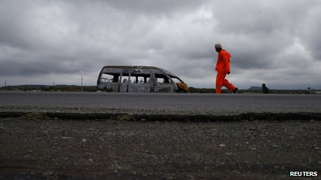 A mineworker walks past the remains of a minibus taxi burnt in strike related violence close to a mine belonging to Anglo American Platinum outside Rustenburg in the North West province, 12 October, 2012