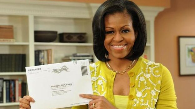 Michelle Obama holds up her absentee ballot