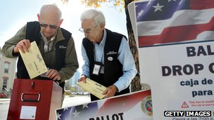 Two men place ballots into a drop-off box
