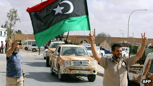 Libyan pro-government forces hold up their national flag as they drive through the streets of Bani Walid