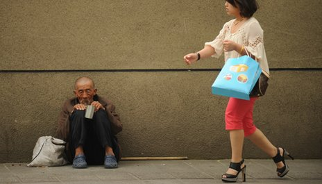 Woman and beggar in Beijing