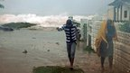 Residents evacuate their home as waves crash in the Caribbean Terrace neighbourhood of eastern Kingston, Jamaica.