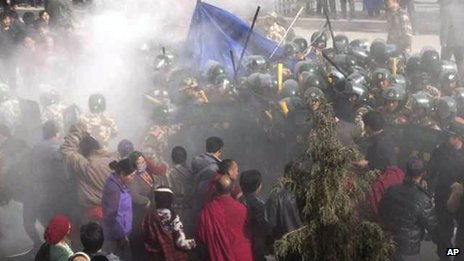 In this photo taken Tuesday 23 Oct 2012 and released by Washington-based International Campaign for Tibet, Chinese paramilitary police officers and residents converge on the body of Dorje Rinchen