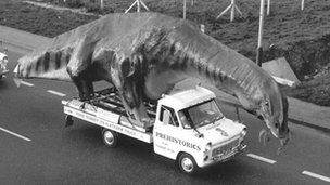 A Transit carries a 49ft long dinosaur model from Kent to the natural history park in Scotland, 1973
