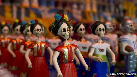 Small skeleton figures on display at the Jamaica flowers market in Mexico City