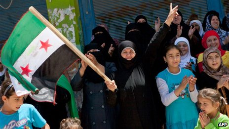 A Syrian woman holds a pre-Baath national flag, which was adopted by the opposition, during an anti-government demonstration after the Friday prayers in the city of Binnish in Idlib province on June 29, 2012.