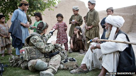 A British female soldier talking to Afghan villagers