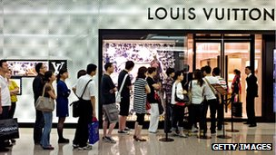 People queue outside a Louis Vuitton store in a Shanghai shopping mall