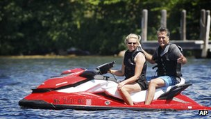 Mitt Romney rides on the back of a jet ski piloted by his wife Ann