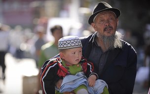 Ethnic Uyghur grandfather holds child